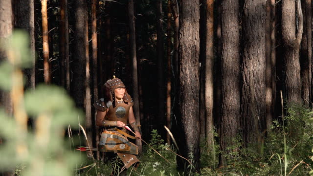 young tatar mongolian archer shoots bow, standing in green forest in afternoon - cacciatore video stock e b–roll