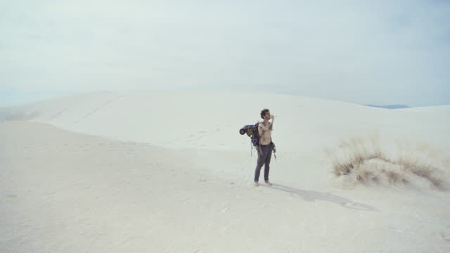 Young tattooed Caucasian man, tourist - hiker with the big backpack, drinking the bottled water in the middle of the sandy desert. White Sands National Monument, New Mexico, USA.  Aerial drone footage. video