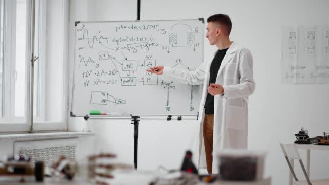 unga lärare i labbrock talar och visar matematisk formel på whiteboard - fysik bildbanksvideor och videomaterial från bakom kulisserna