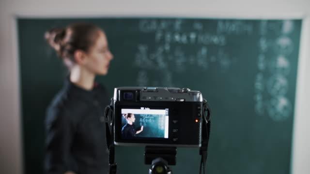 młody nauczyciel nauczający zdalnie za pomocą kamery do strumieniowego przesyłania lekcji - instruktor filmów i materiałów b-roll