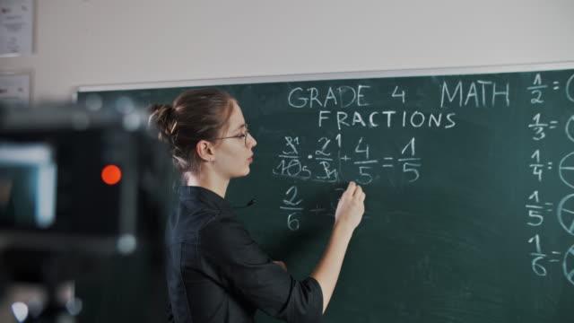 젊은 교사 교육 원격으로 사용하여 카메라로 수업을 스트리밍 - 성인 전용 스톡 비디오 및 b-롤 화면