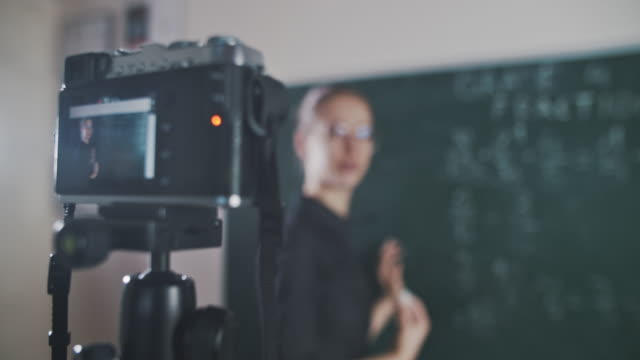 Young teacher teaching remotely using camera to stream lesson Young teacher teaching remotely using camera to stream lesson.  BMPCC 4K rack focus stock videos & royalty-free footage