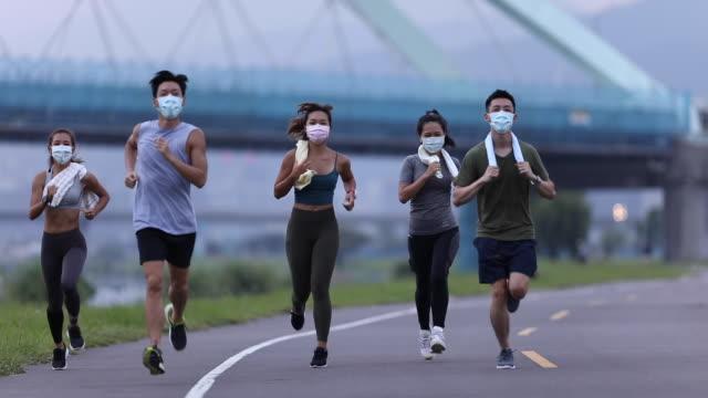 Young team wearing masks jogging at dusk