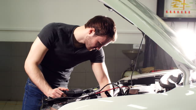 Young Technician Man Making Engine Service of Car in Garage video