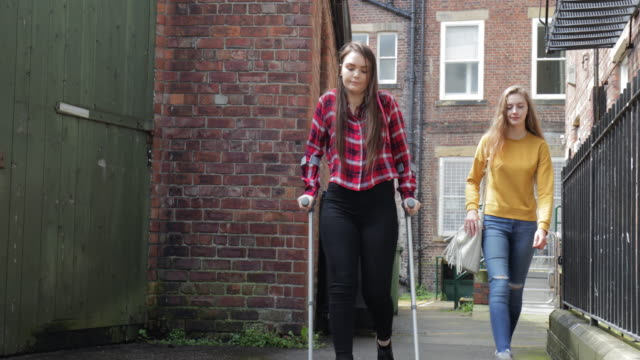 Young Teen Girl in Crutches Walking Home A young teen girl in crutches walking home by herself while bystanders do nothing crutch stock videos & royalty-free footage