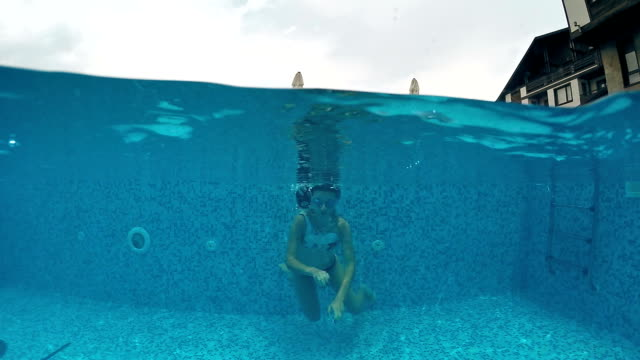 young teen with googles diving in outdoor pool, gopro dome shot, slow motion - google filmów i materiałów b-roll