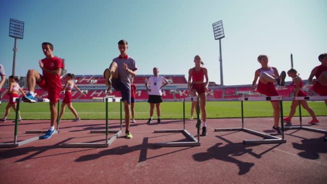 Young teenage athletes hurdling on training