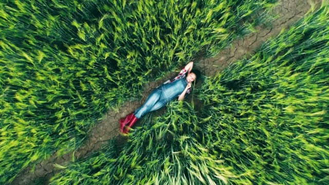 Young teenage girl farmer relaxing,laying in rural,green wheat field,real time