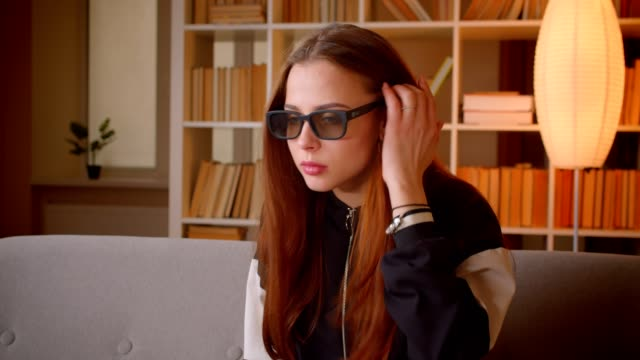 Young teenage girl in 3d glasses watches horror movie on TV gets scared on bookshelves background at home.