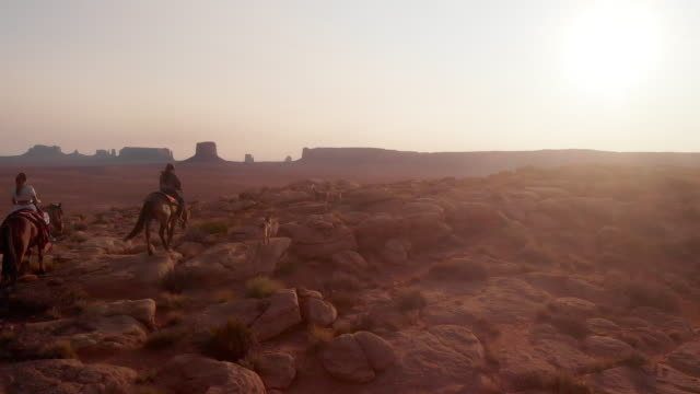 Young Teenage Native American Navajo Brother and Sister Riding Their horses Bareback in the Vast Sweeping Desert in Northern Arizona at the Monument Valley Tribal Park at Dusk or Dawn