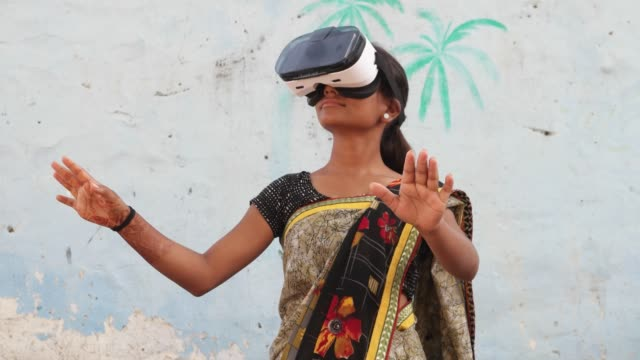 Young teenager girl wearing VR virtual reality headset working games enjoy music playing engage cinema film hands point cutting edge contemporary wireless communication technology surreal India rural Indian teenager girl in rural setting at home residence using technology computer mobile phone content happy freedom wearing traditional sari sari stock videos & royalty-free footage