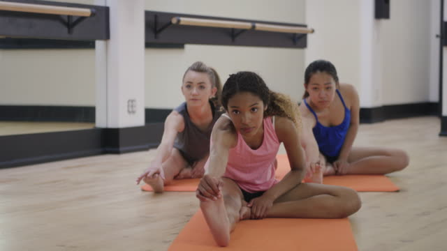 Young teenagers stretching together in a studio Young teenagers stretching together in a studio dance studio stock videos & royalty-free footage