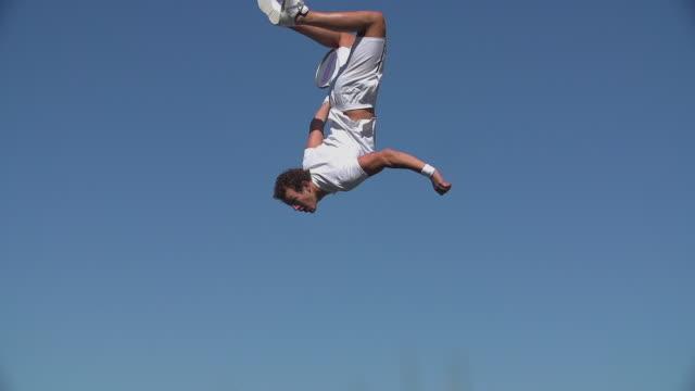 A young tennis player having fun backflips and returns tennis ball. video
