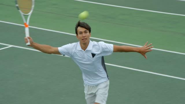 Ein junger Tennisspieler rennt über den Platz, streckt und verpasst den Schuss. – Video