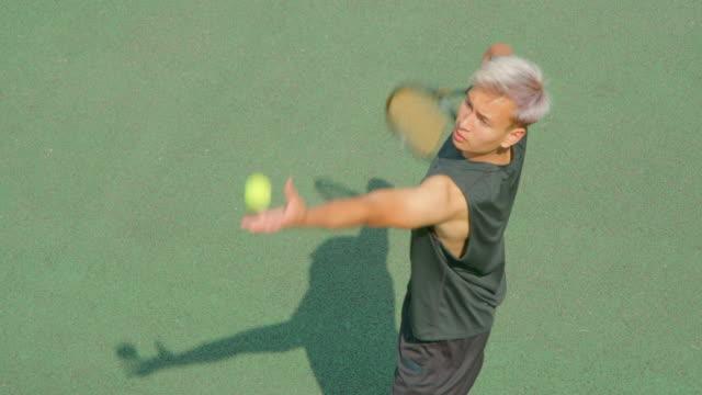 Ein junger Tennisspieler bedient in Zeitlupe. – Video