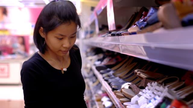vídeos y material grabado en eventos de stock de joven tailandesa señora escogiendo zapatos en el super mercado - moda playera