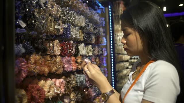 молодая тайская женщина выборе scrunchy для волос в магазине аксессуаров - аксессуар для волос стоковые видео и кадры b-roll