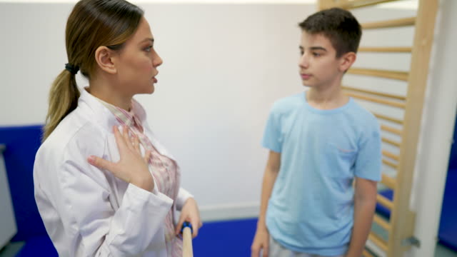 vídeos de stock, filmes e b-roll de jovem terapeuta explica ao jovem paciente como ele fará o próximo exercício - ortopedia