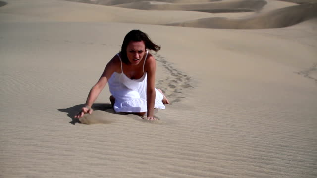 Young thirsty woman crawling in sand video
