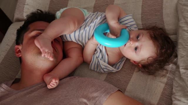 vídeos de stock e filmes b-roll de young tired father sleep near a little child - cansado