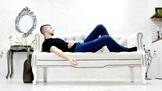 vídeos y material grabado en eventos de stock de joven hombre cansado durmiendo en el sofá - solteros jóvenes