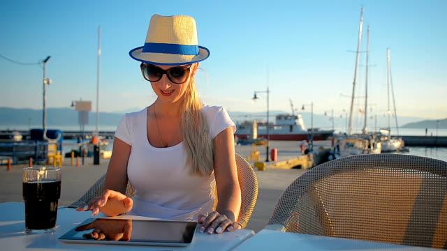 vídeos de stock, filmes e b-roll de jovem turista se comunica em redes sociais sobre o tablet em um café de verão - marina