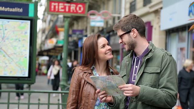 vídeos de stock, filmes e b-roll de jovem casal de turistas olha para o mapa fora de uma estação de metrô de paris e decide qual caminho seguir. - turista