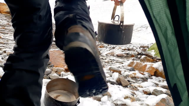 Young tourist getting out of a tent and takes a pot in snowy mountains in slo-mo