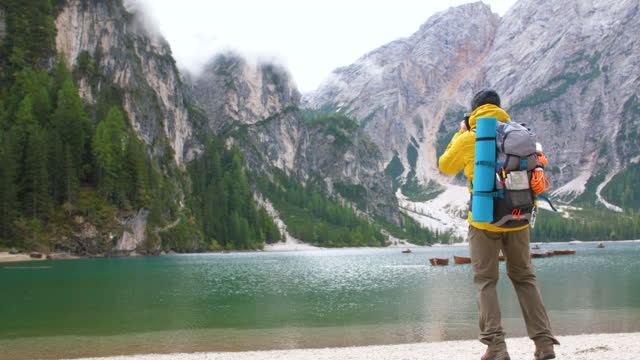 Young tourist hiker man taking pictures at beautiful alpine lake Lago Di Braies (Pragser wildsee) in Trentino, Dolomites mountains, Italy.