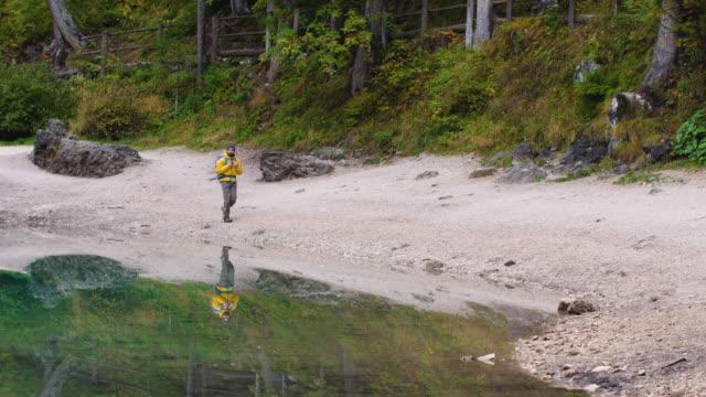 vídeos de stock e filmes b-roll de young tourist hiker man walking at beautiful alpine lake lago di braies (pragser wildsee) in trentino. traveling dolomites mountains, italy. - margem do lago