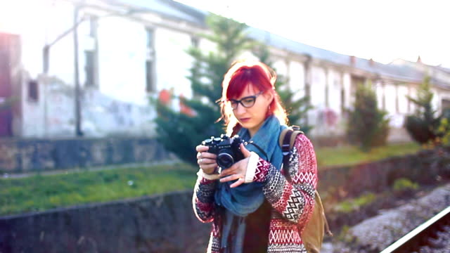 Young tourist photographer woman with camera video