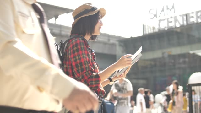 Young tourist woman exploring city map while traveling, vacation concept