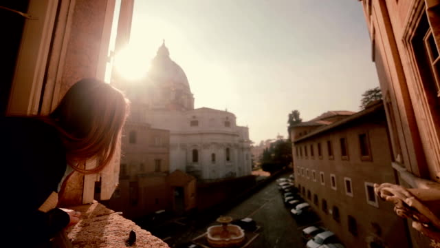 Young tourist woman looking at the window, the cityscape of Saint Peter Basilica in Vatican. Girl exploring the sight video