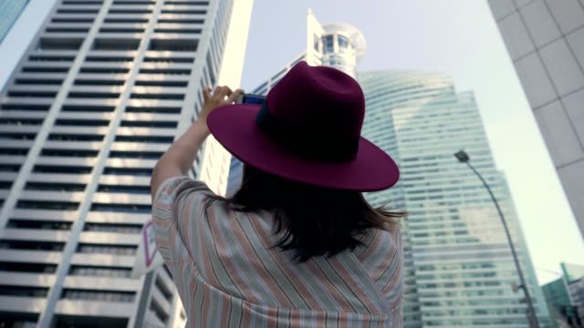 Young tourist woman taking photo with smart phone in Singapore city