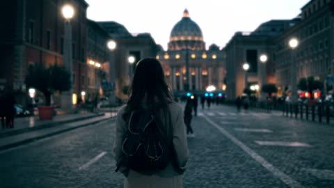 vídeos y material grabado en eventos de stock de mujer joven turista a pie de piazza di spagna, cerca de la catedral de saint peter. chica mirando a su alrededor, explorar lugares de interés - turismo vacaciones