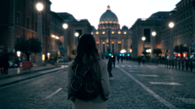Young tourist woman walking in Piazza di spagna near the Saint Peter Cathedral. Girl looking around, exploring sights video
