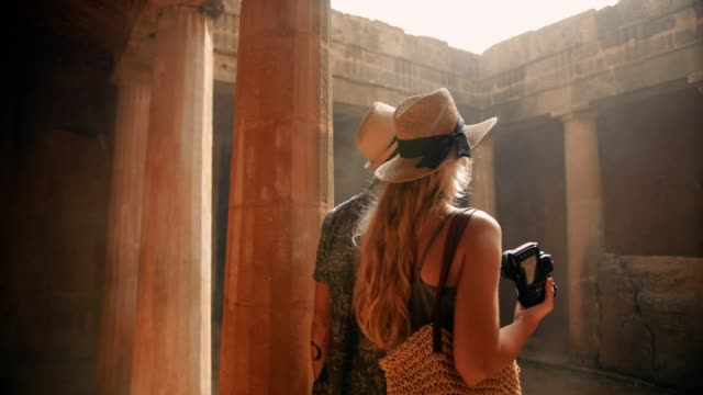 Young tourists couple in Greece taking photos of ancient columns video