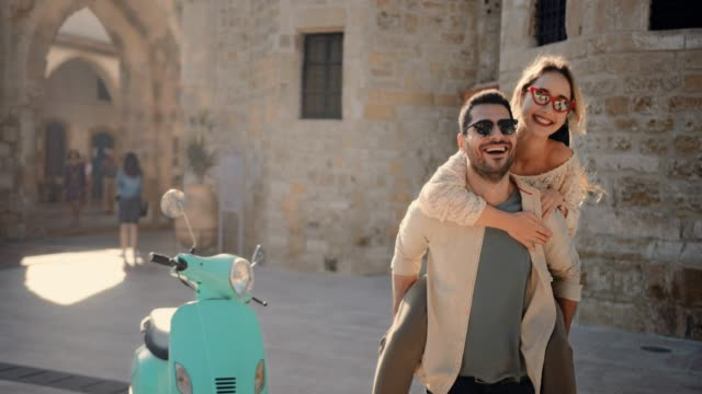 unga turister par med skoter att ha kul med piggyback ride - pojkvän bildbanksvideor och videomaterial från bakom kulisserna