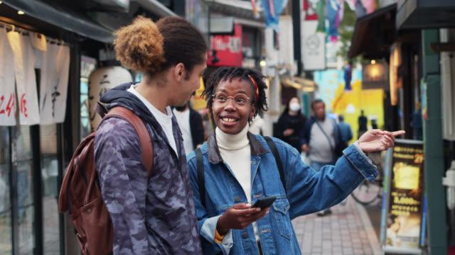 日本で電話を見ている若い観光客 - アフリカ民族点の映像素材/bロール