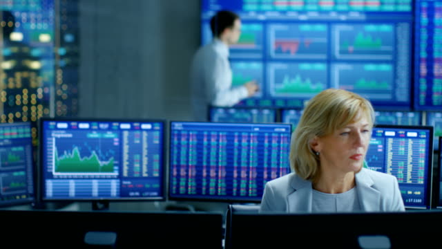 young trader walks into market exchange room, senior sales force representative works on her computer. room has screens with ticker numbers and graphs. - обслуживание стоковые видео и кадры b-roll