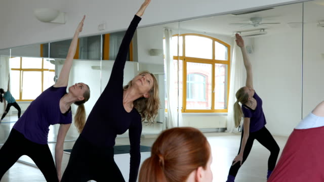 Young trainer instructing women in yoga class video