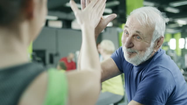 Young trainer with senior client at gym video