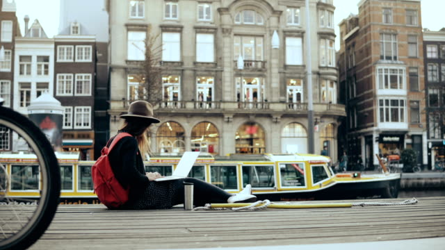 4K Young traveler girl sits outside with laptop. Lively Amsterdam old town street, pigeon, boat and bikes passing by video