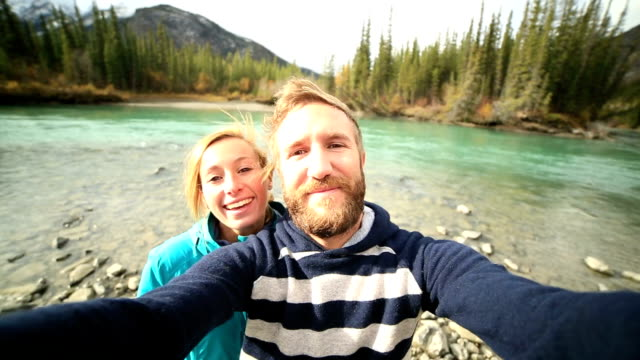 Young traveling couple by the river taking a selfie portrait video