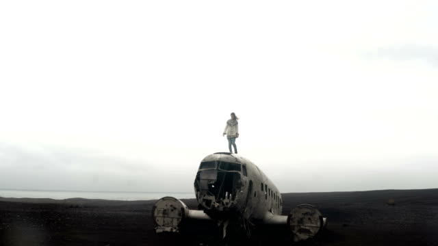 Young traveling woman standing on the top of breaker DC-3 BMC plane on the black beach in Iceland. Hair waves on wind.