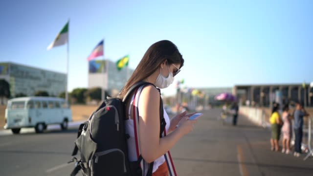 Young traveller woman walking and using mobile phone in Brazil - wearing face mask