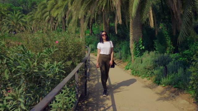 vidéos et rushes de tendance jeune belle femme bronzée aux cheveux noirs promenades le long du chemin d'accès entre palmiers tropicaux dans le parc guell de barcelone. concept de voyage. 4k - lieu sportif