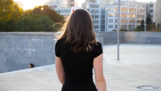 都会の通りを歩いている黒いドレスの若い認識できない少女。美しいビジネスウーマンが街に行く。都会の環境で働く女性。リアビュースローモーションクローズアップ - 後に続く点の映像素材/bロール