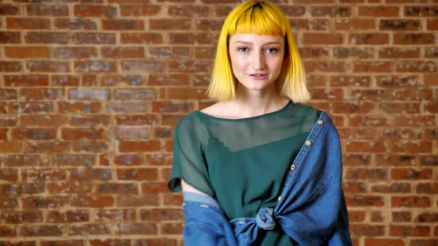 Young unusual woman with yellow hair dancing and looking at camera, isolated over brick wall background video