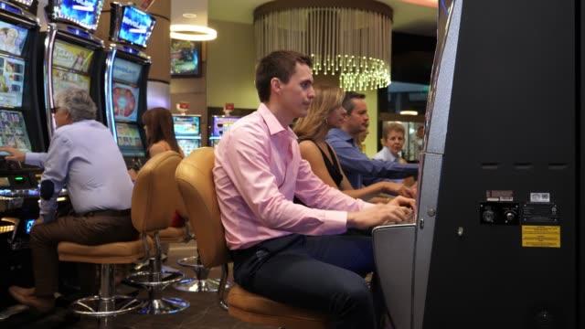 ung upprörd man spelar på enarmade banditer på casino förlora pengar - missbruk koncept bildbanksvideor och videomaterial från bakom kulisserna